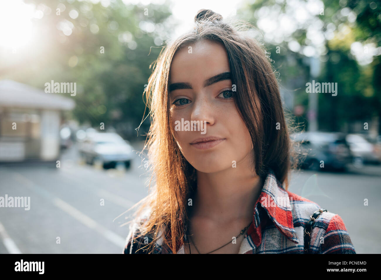 Close Up Portrait Of Happy Young Woman In City With Green