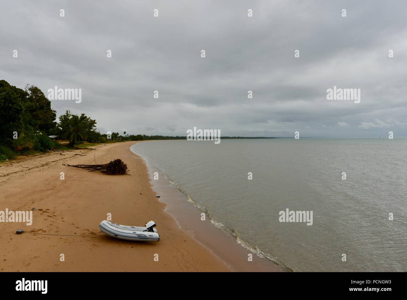 A small inflatable boat on the beach at Cardwell, Queensland, Australia - Stock Image