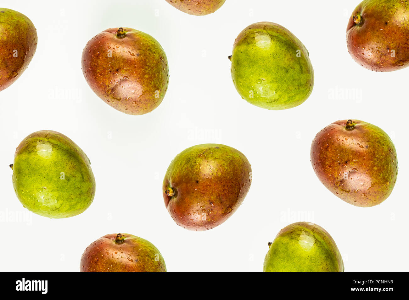 Isolated mango pattern or wallpaper on white background. Summer concept of fresh ripe whole mango fruits shot from above - Stock Image
