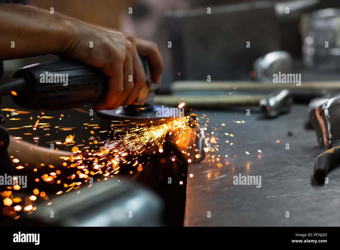 Man hands treating metal parts of hardware in a workshop with angle grinder. Male metal worker polishing and finalising piece of medieval armour suit. - Stock Image