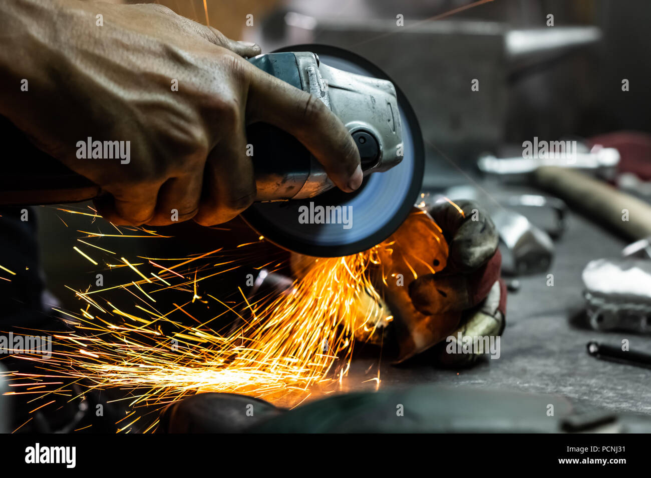 Male metal worker polishing and finalising piece of medieval armour suit. Man hands treating metal parts of hardware in a workshop with angle grinder. - Stock Image