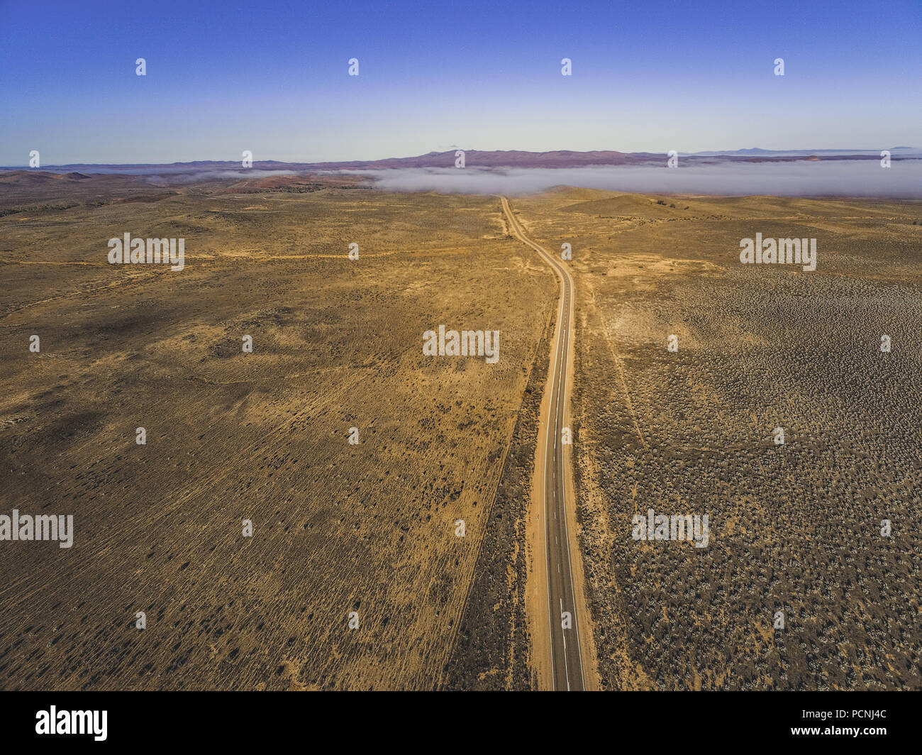 Highway passing through Australian outback desert leading to mountains under low cloud - aerial view - Stock Image