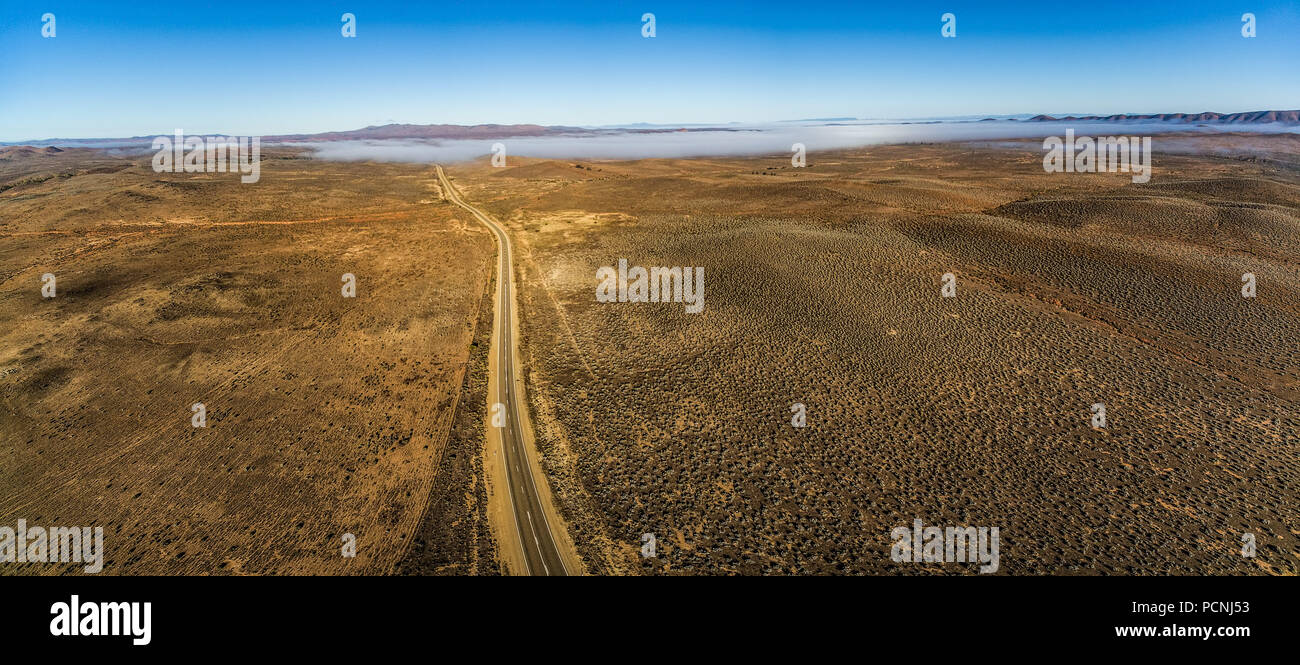 Rural highway passing through Australian outback desert leading to mountains under low cloud - aerial panorama - Stock Image