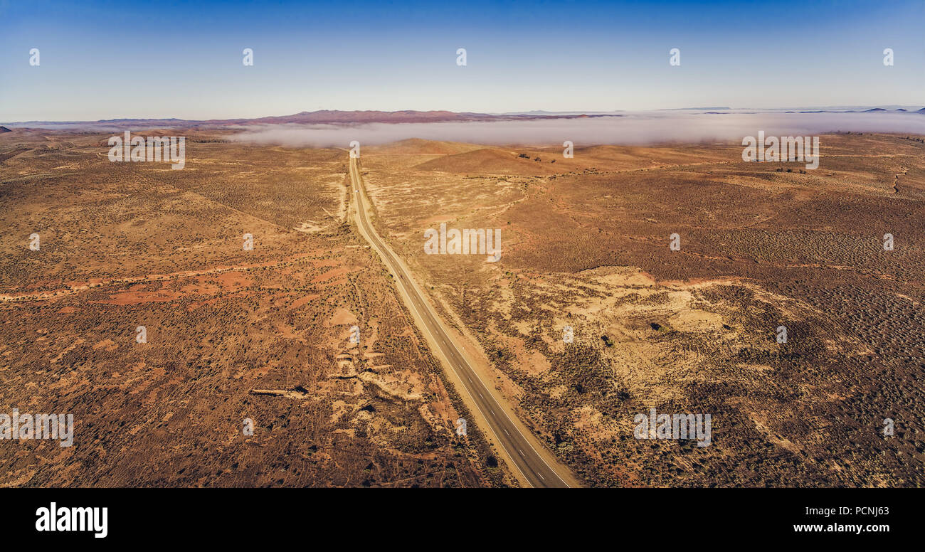Countryside highway passing through Australian outback desert leading to mountains - aerial panorama - Stock Image