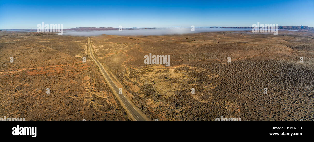 Countryside highway passing through Australian outback desert leading to mountains - wide aerial panorama - Stock Image