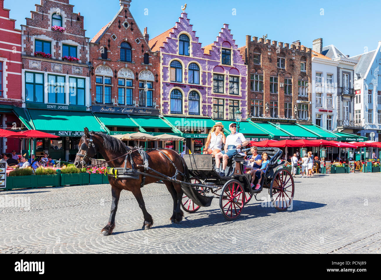 Tourists being taken on city tour with a horse and trap in the Markt Square, Bruges - Stock Image