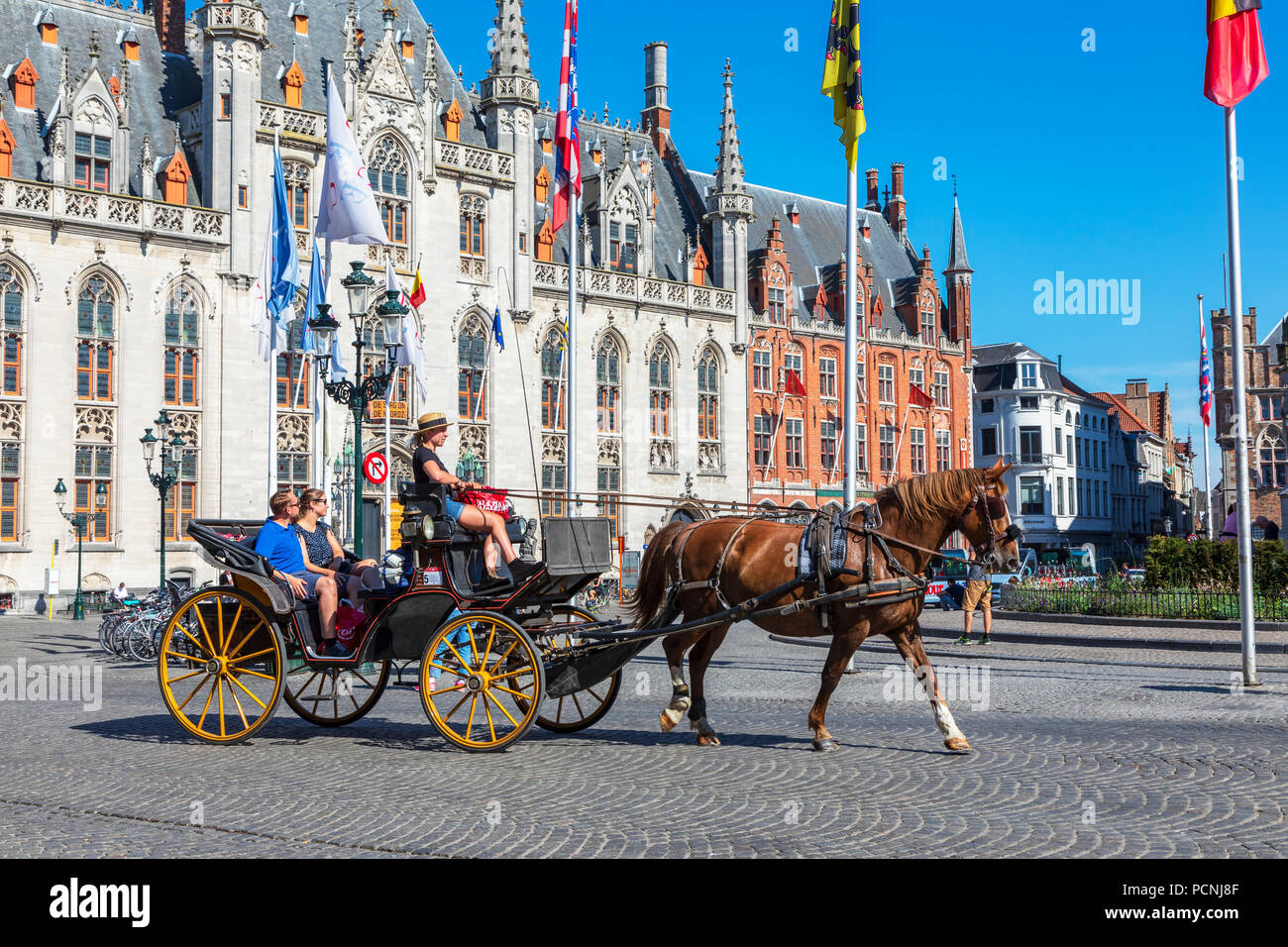 Tourists being taken on a city tour with a horse and trap, Markt Square, Bruges, Belgium - Stock Image