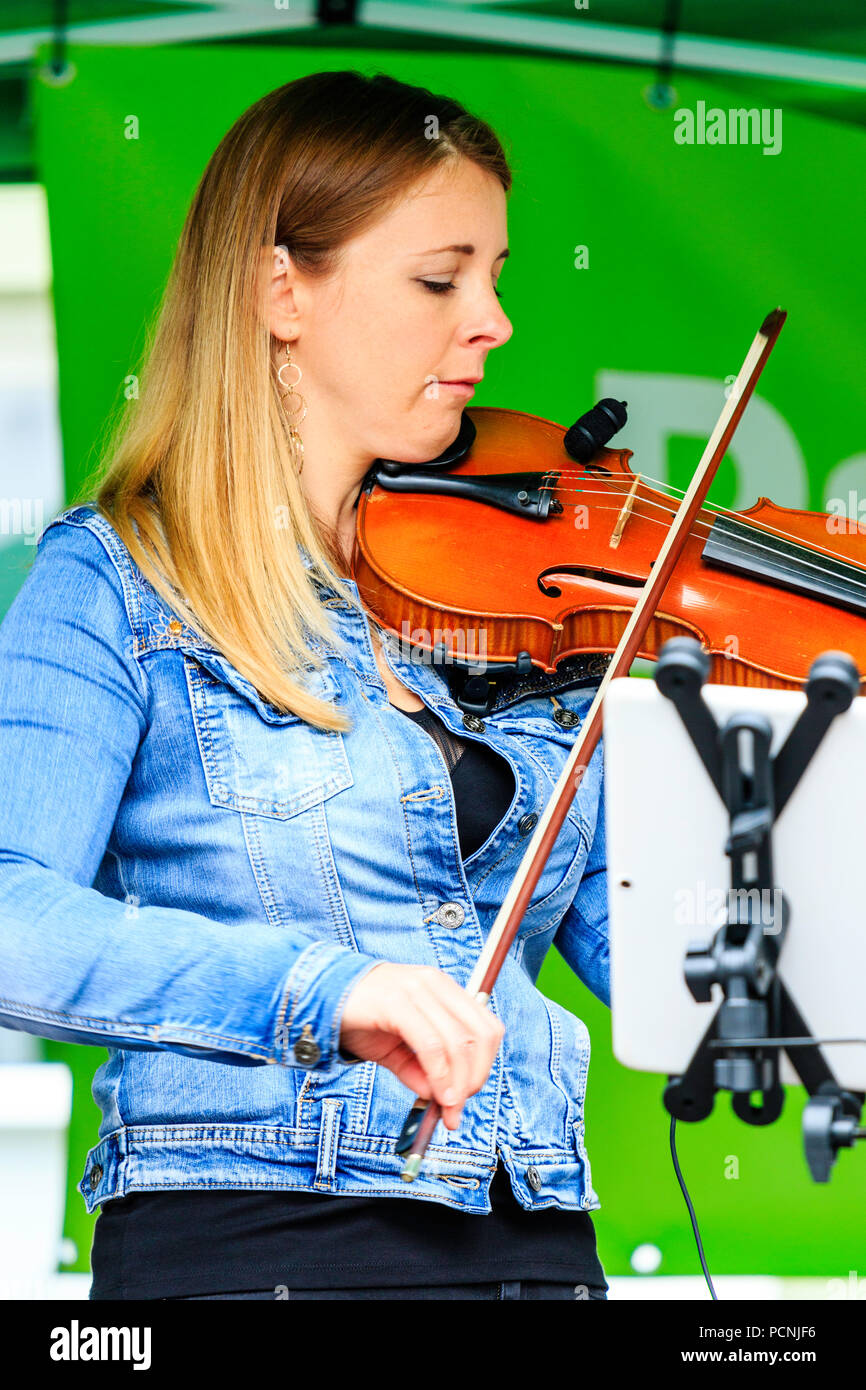 Caucasian woman, 20s, playing fiddle, violin at open air