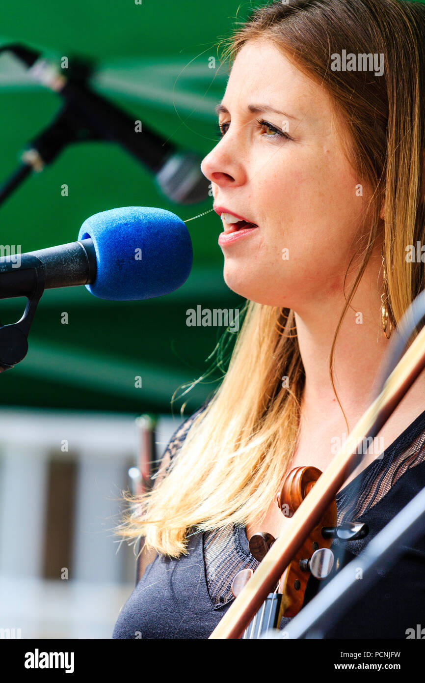 Caucasian woman, 20s, playing fiddle, and singing at open air concert. French folk rock band Triskelles performing an open-air gig - Stock Image