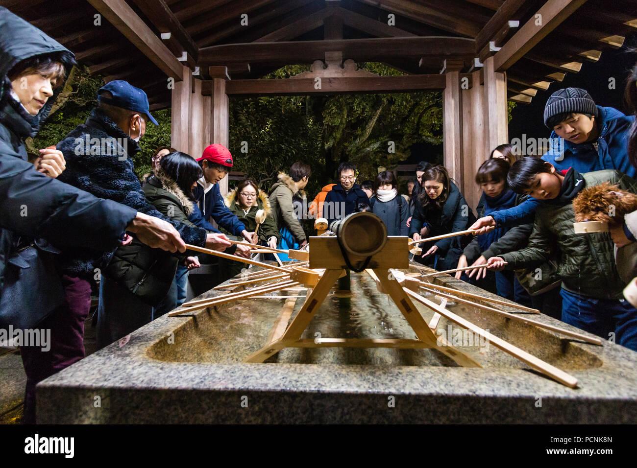 Shogatsu, New Year, Nishinomiya Shinto shrine, Japan. Purification basin, chozuya, packed at midnight with people arriving for Hatsumode, first visit. - Stock Image