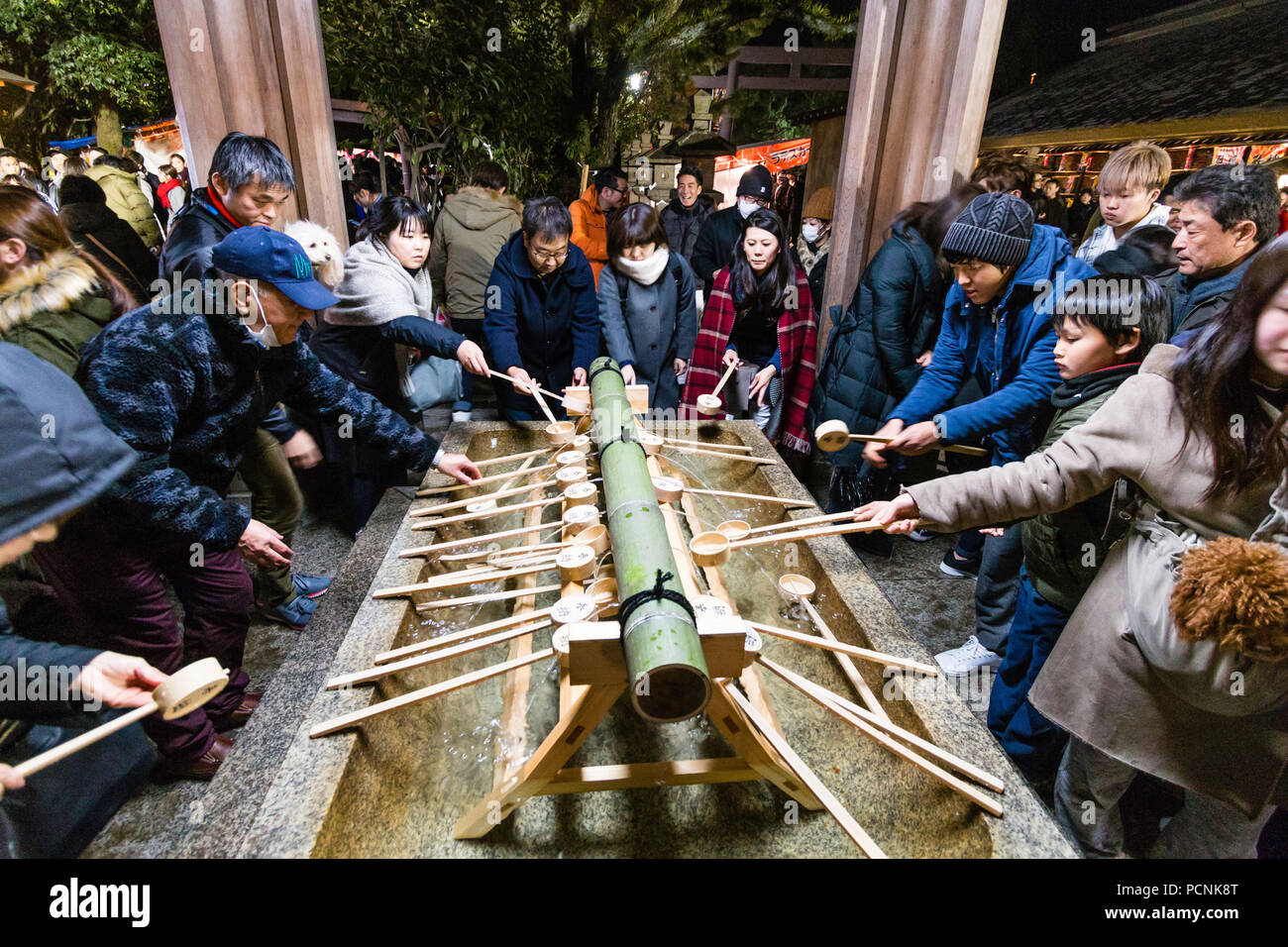 Shogatsu, New Year, Nishinomiya Shinto shrine, Japan. Purification basin, chozuya, packed at midnight with people arriving for Hatsumode, first visit. - Stock Image