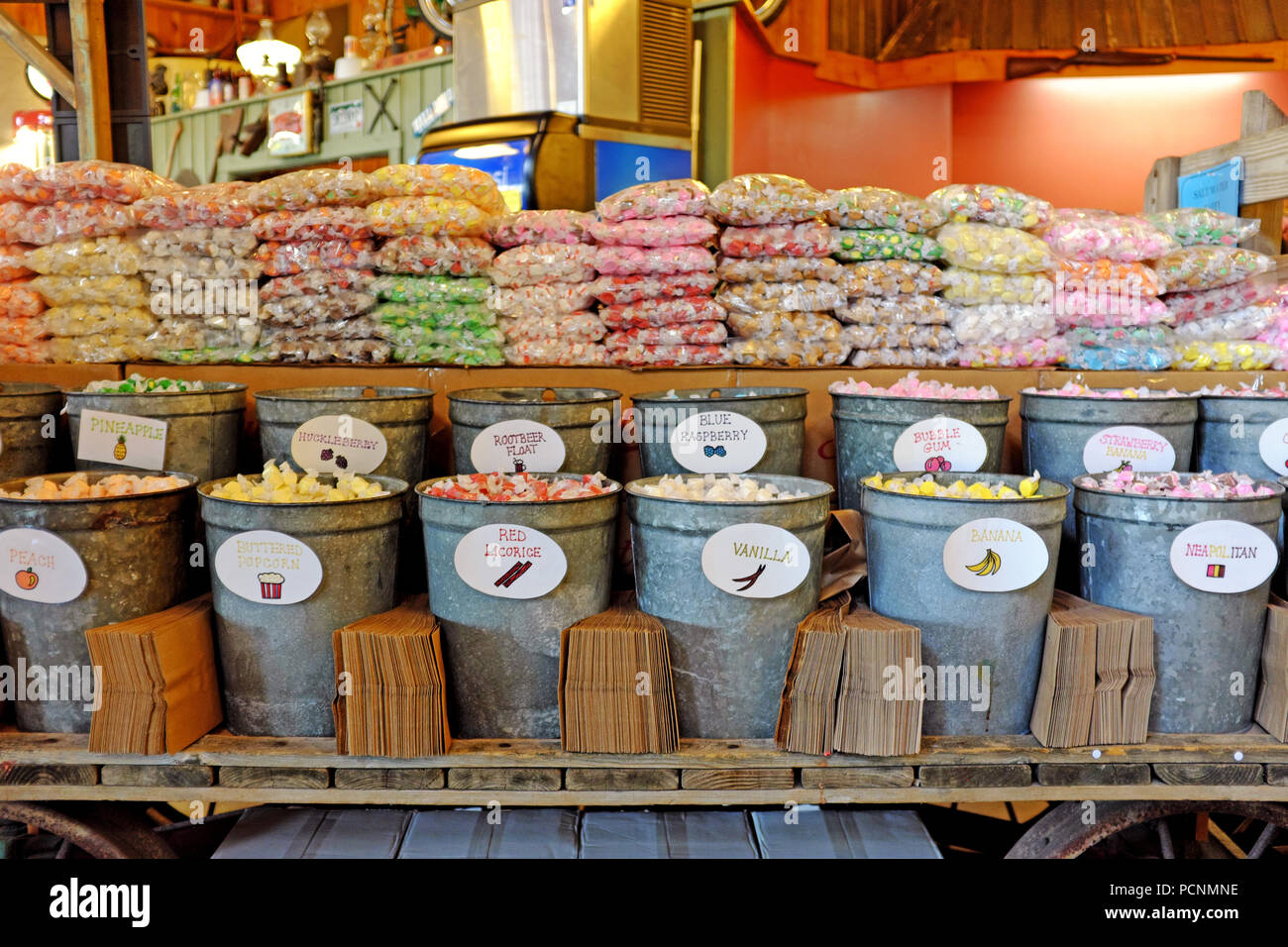 Salt-water taffy for sale with individual wrapped pieces filling tin buckets which people then put in brown bags and paid for by weight. - Stock Image