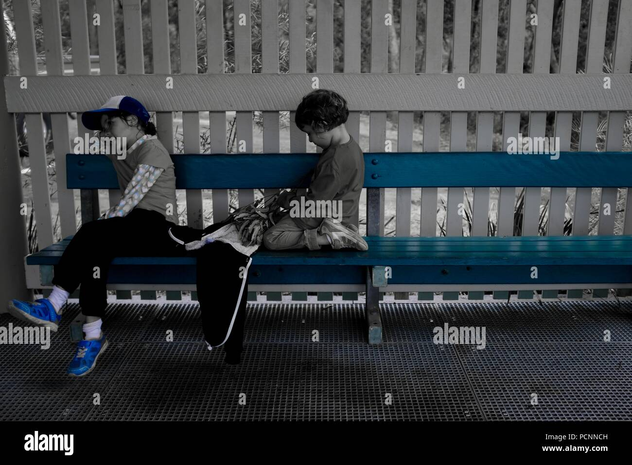 Two girls sitting on a bench, blue filter, Cardwell, Queensland, Australia - Stock Image