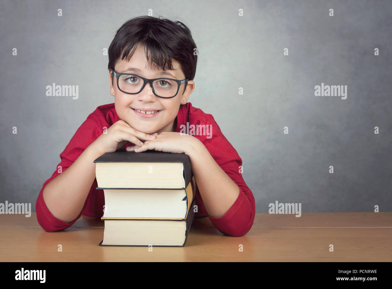 smiling little boy leaning on books on a table on black background - Stock Image