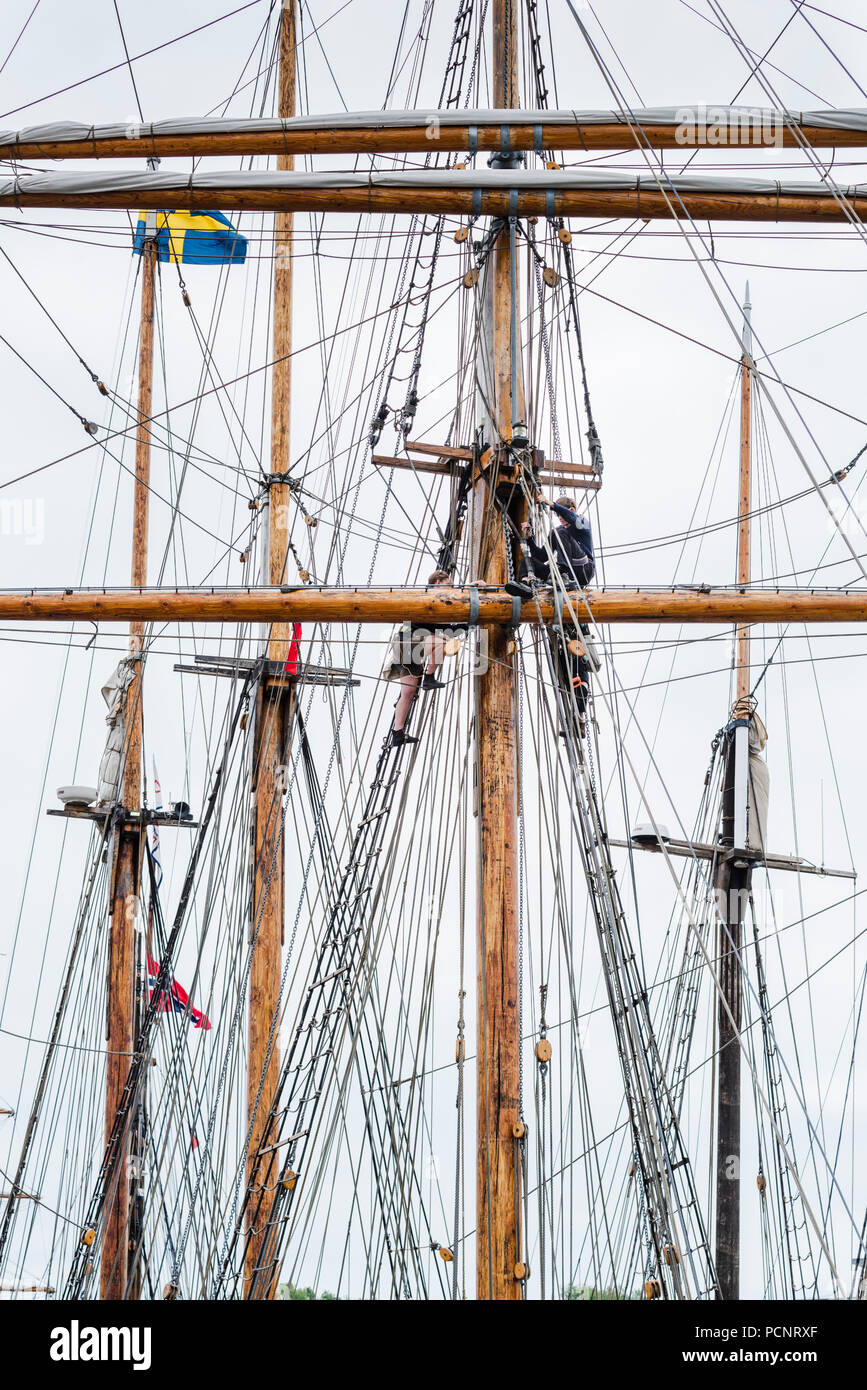 Sailors working on the rigging of a sailing ship in harbour during the 2018 Tall Ships Race - Stock Image