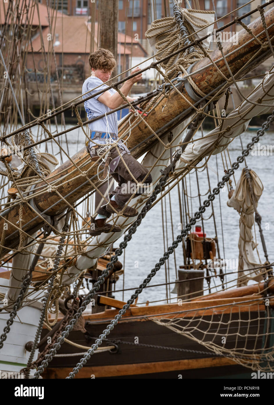 Sailor working on the rigging of a sailing ship in harbour during the 2018 Tall Ships Race - Stock Image