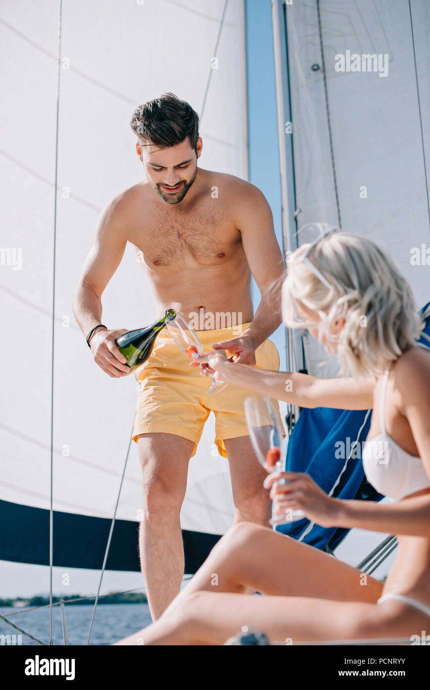 handsome shirtless man in swim trunks pouring champagne into glass of girlfriend on yacht - Stock Image