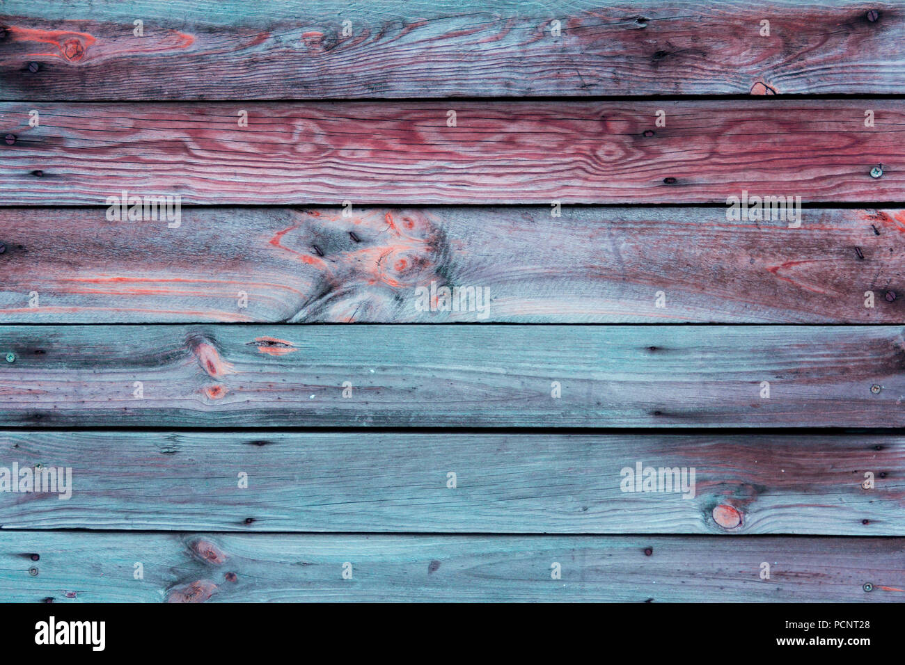 Close-up of the multicolor surface (wall, floor or overhead) made of wooden plank, panel or board in the turquoise, blue, red, claret, coral shades Stock Photo