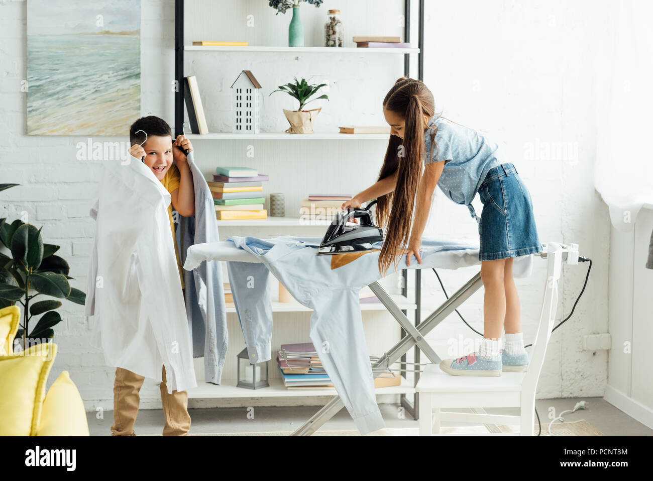disobedient siblings ironing clothes at home - Stock Image