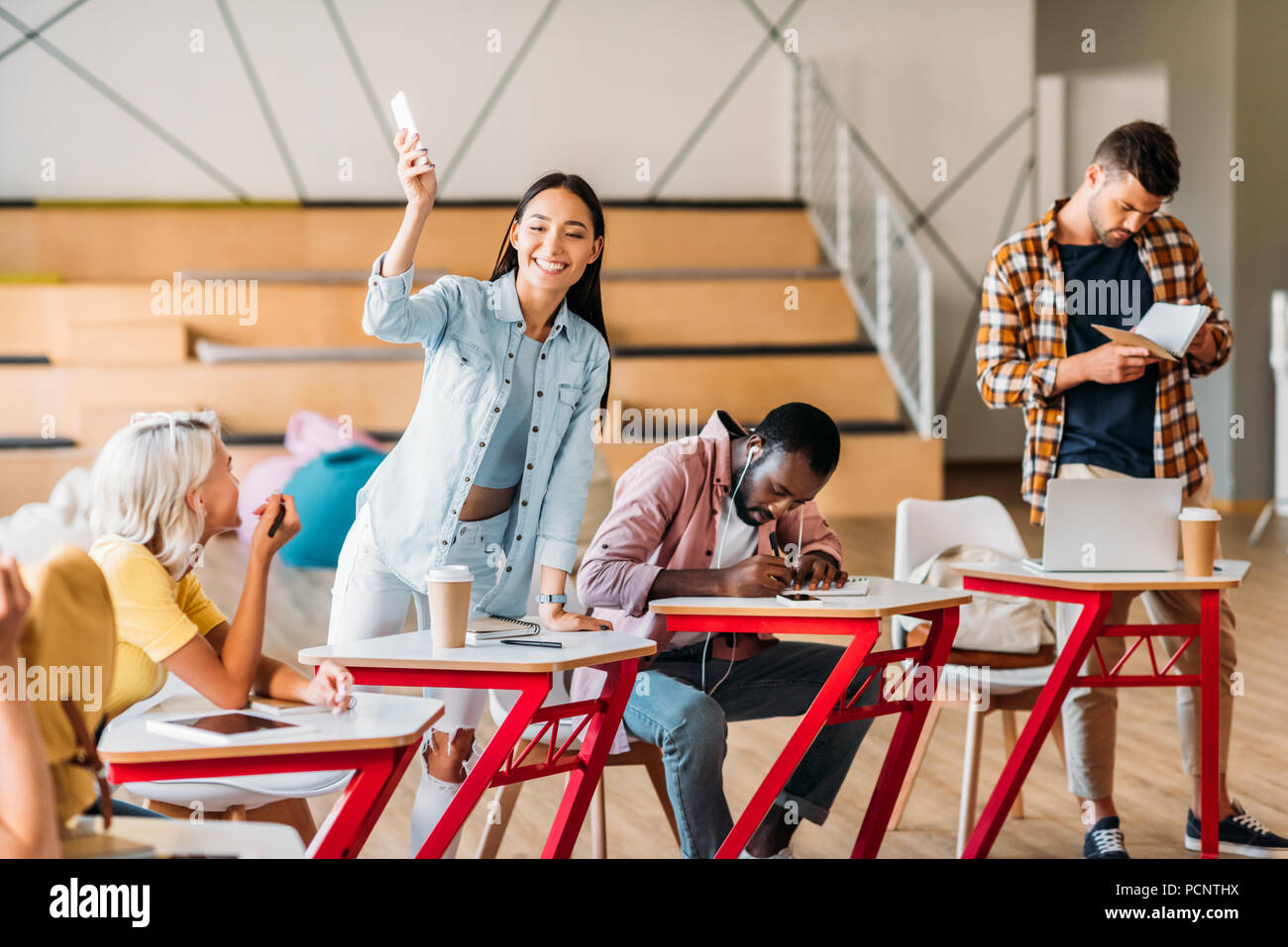 happy young students spending time together in lecture room Stock Photo