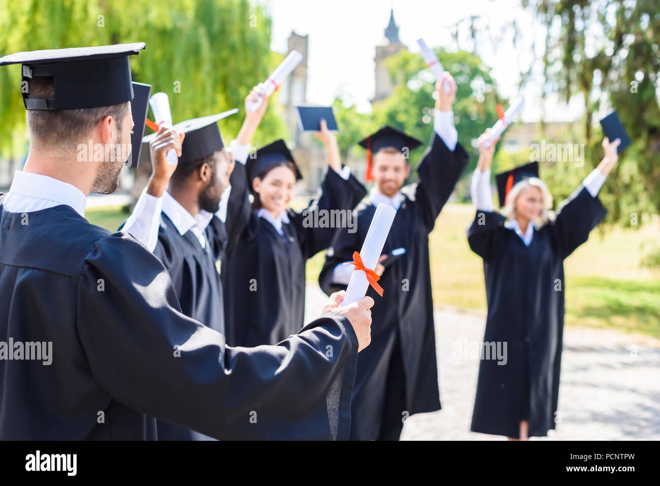 young happy students celebrating graduation together on college square - Stock Image