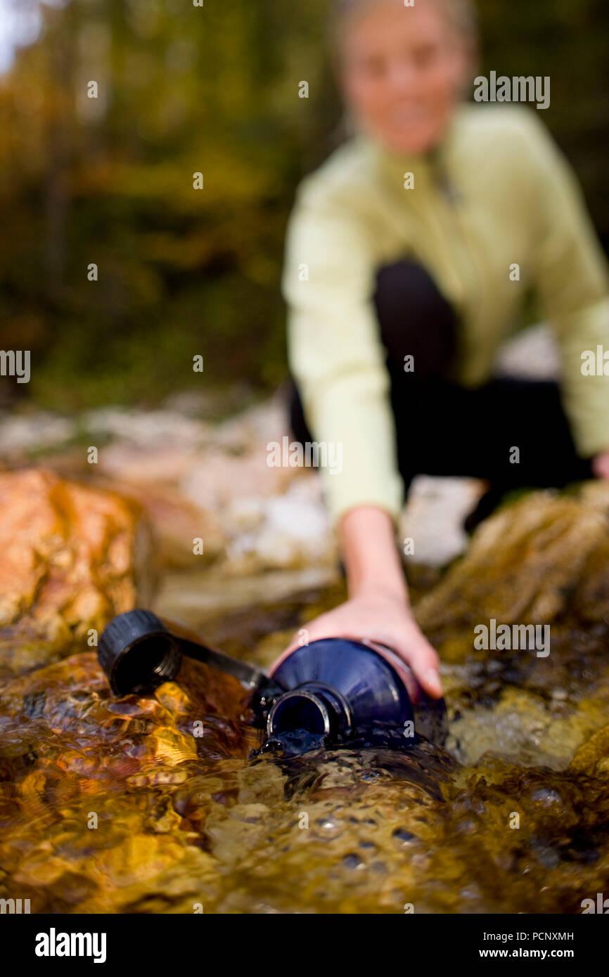 refill a drinking bottle on the creek, in the Reintal, close Garmisch, Wetterstein mountains, Upper Bavaria, Bavaria, Germany - Stock Image