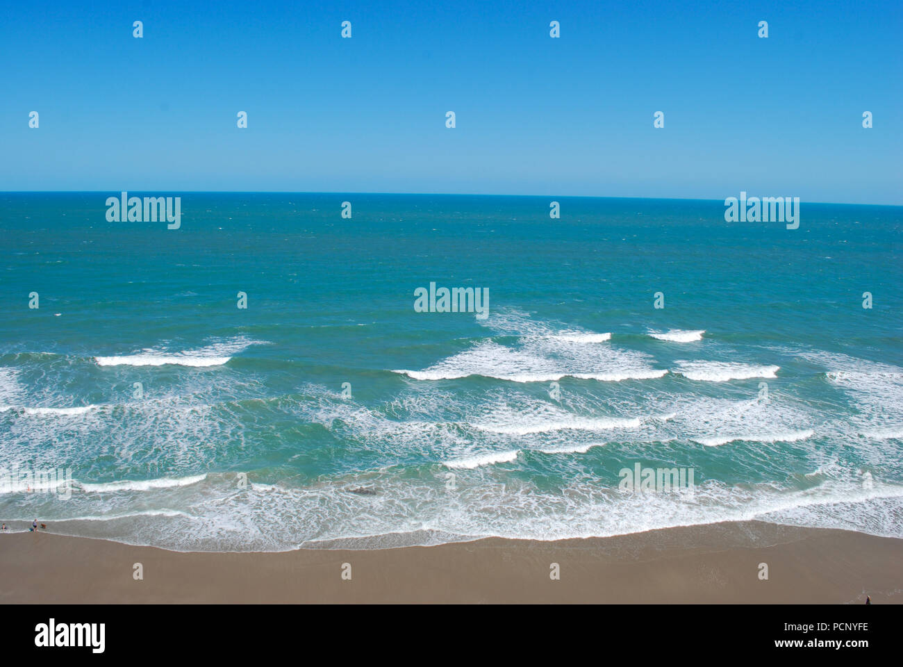 Drone view on ocean waves. Panoramic view with the emerald water of the ocean and white waves. Sea shore emerald water. Stock Photo