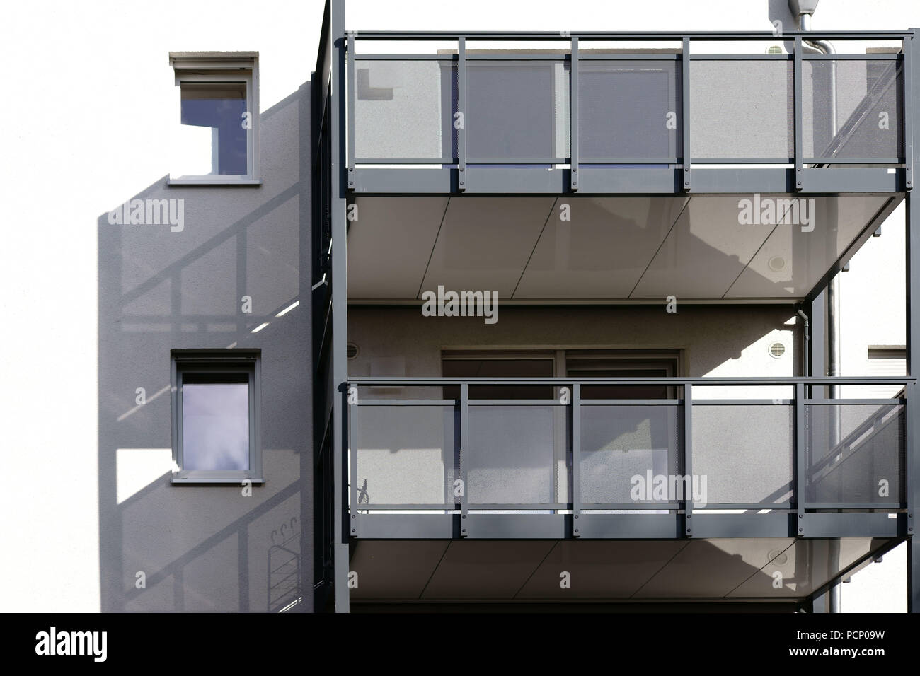 A new and modern balcony of an apartment and apartment building casting shadows. Stock Photo