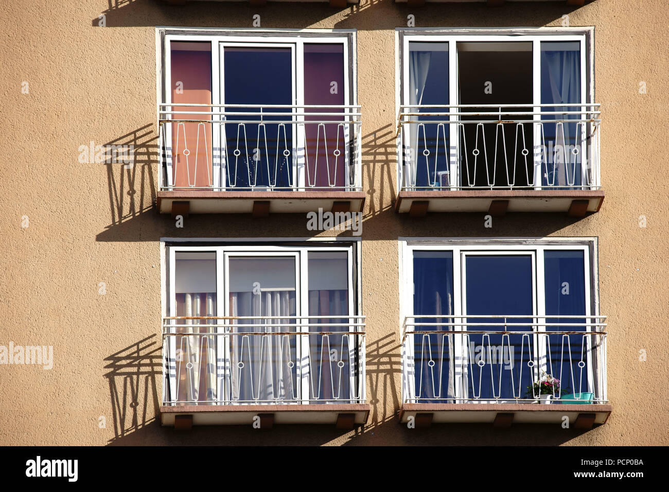 The railings of small balconies of an apartment building casting shadows. Stock Photo