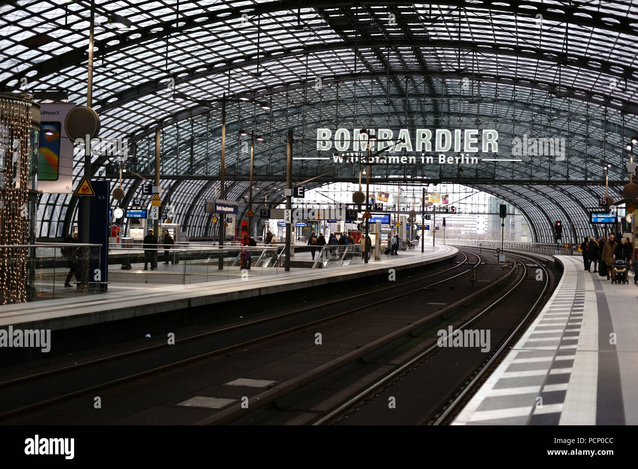 A platform of Berlin's central station with travellers and a distinctive roof construction in Berlin. - Stock Image