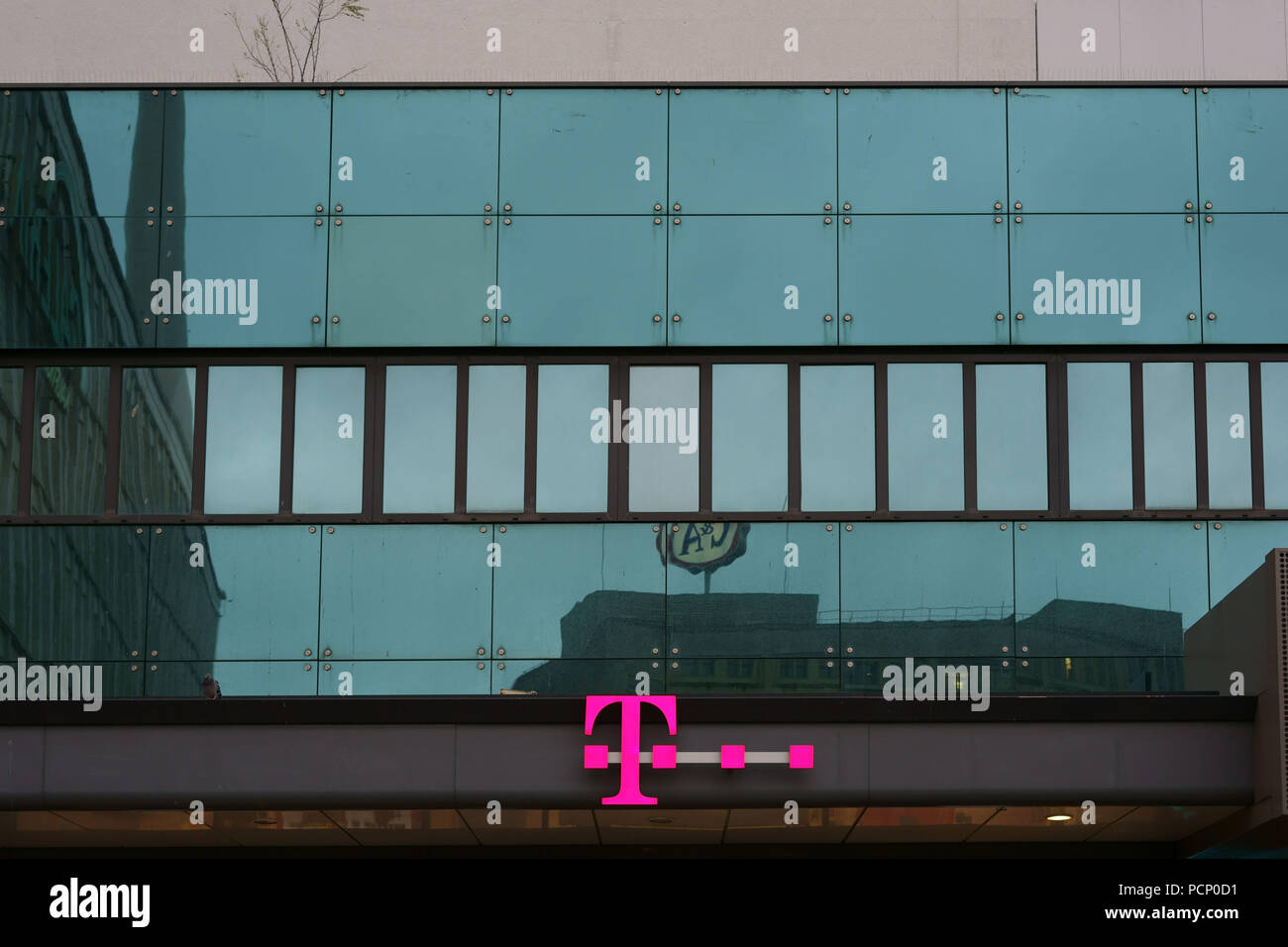 The logo of a Telekom shop on the modern glass facade of a department store on Berlin's Alexanderplatz. - Stock Image