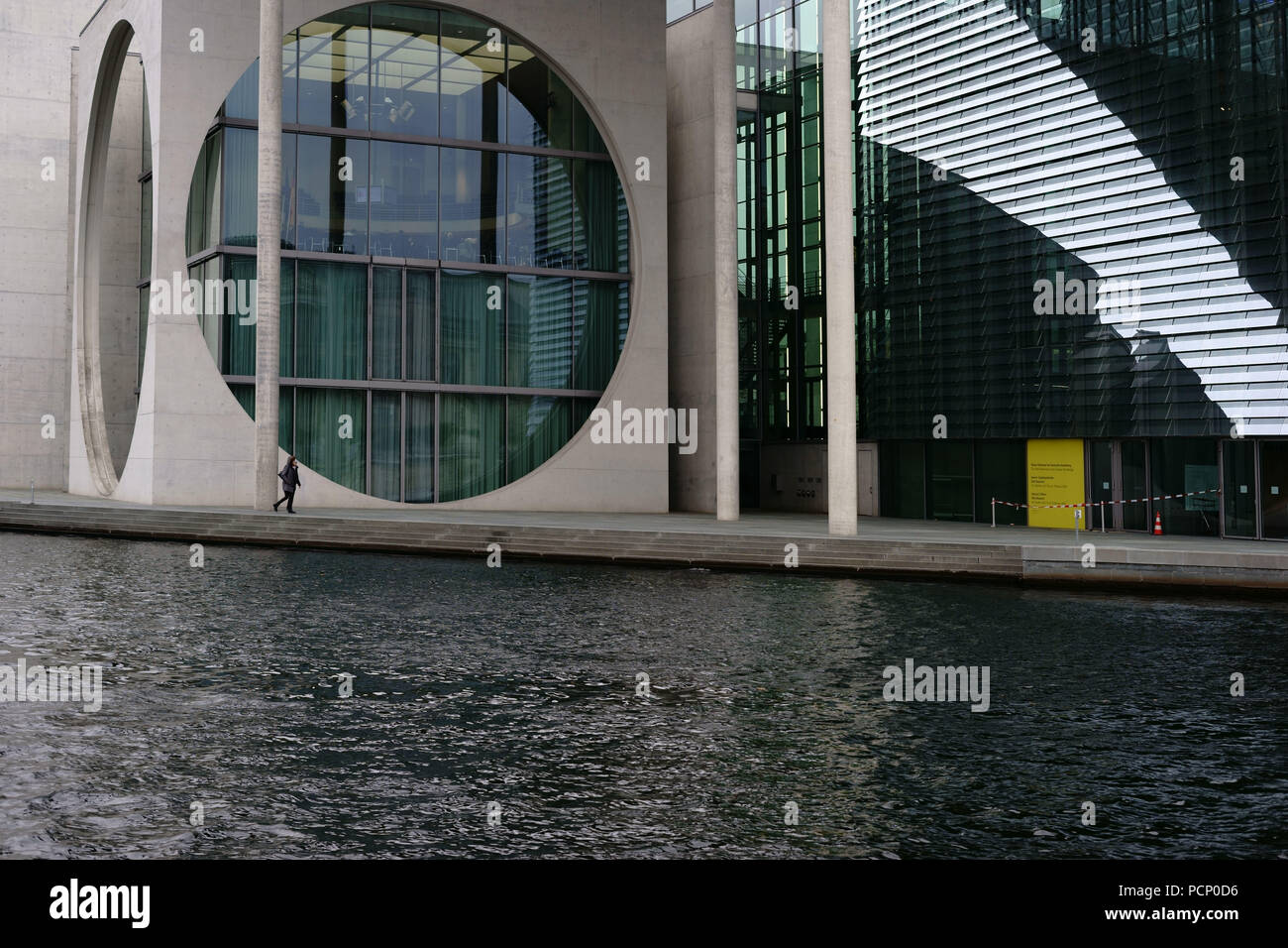 A pedestrian walking along the river Spree pasting the modern architecture of the Marie-Elisabeth-Lüders house in Berlin. Stock Photo