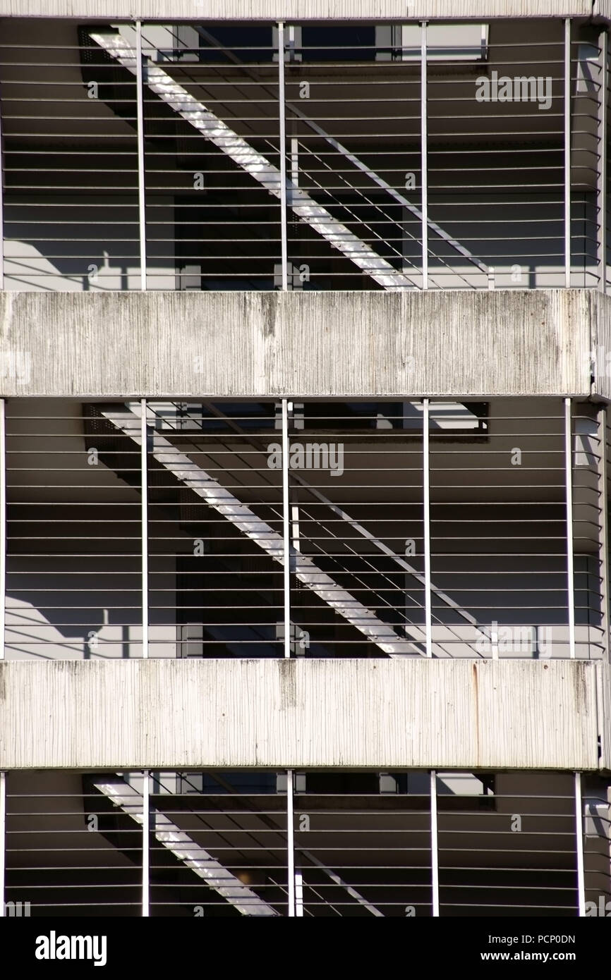 The various floors and levels of a parking garage with stairs behind bars and concrete ceilings. - Stock Image