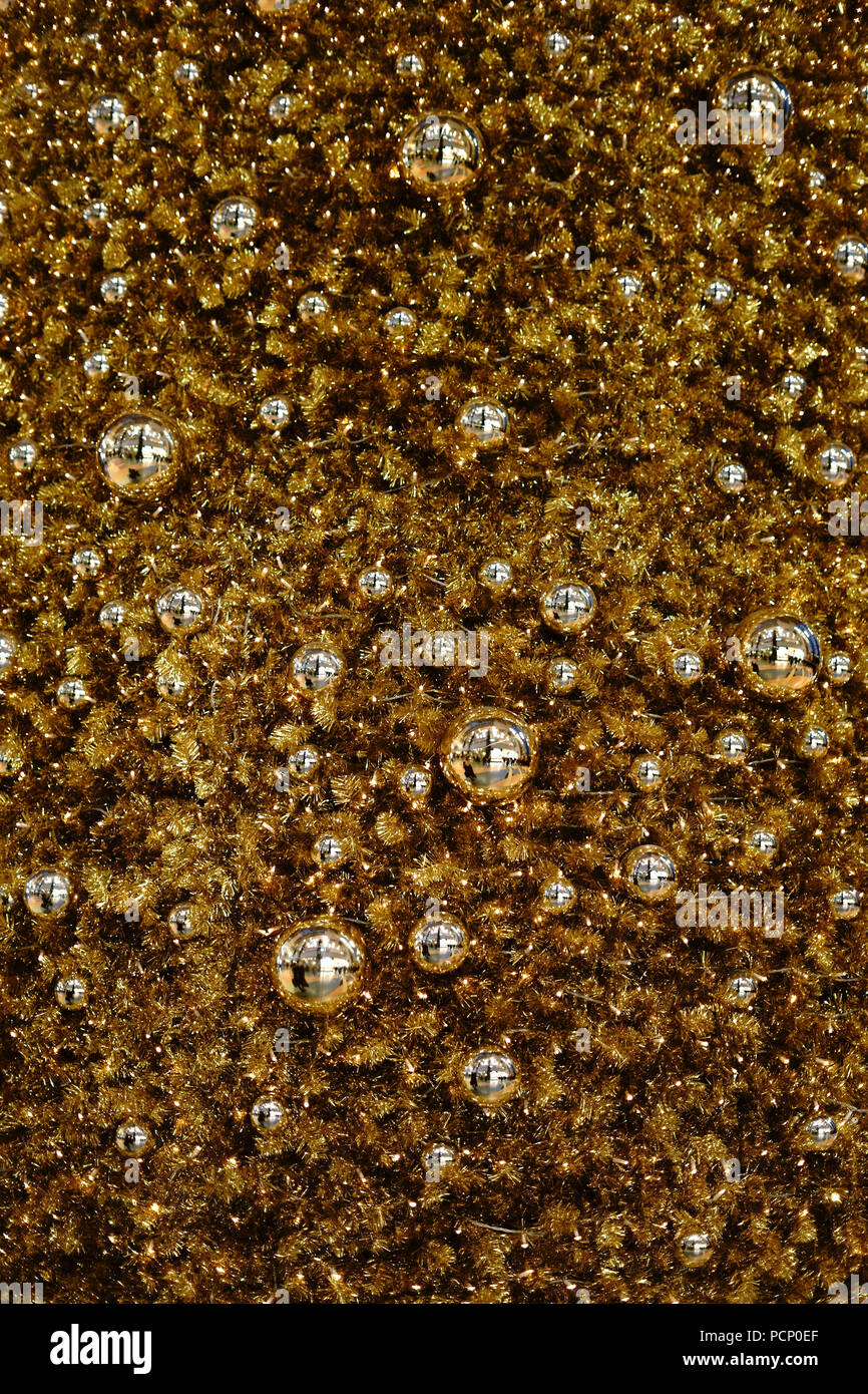 Golden Christmas tree balls as well as tinsel and gold-painted Christmas tree decorations on a Christmas tree. - Stock Image
