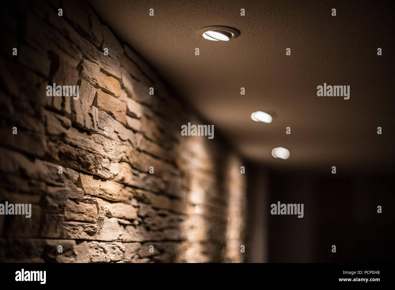 Integrated ceiling spots halogen radiating on a stone wall - Stock Image