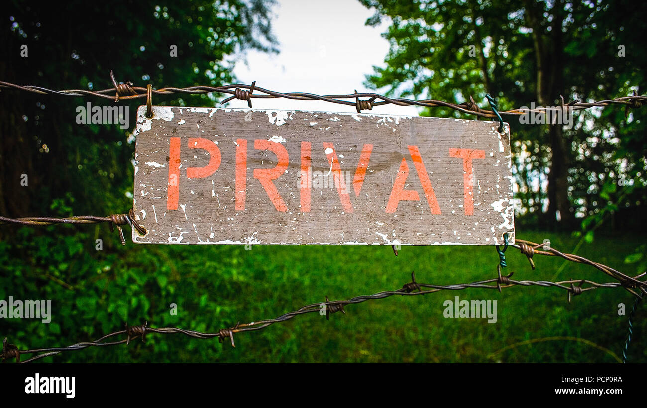 Weathered sign with the words 'Privat', barbed wire fence, private property - Stock Image