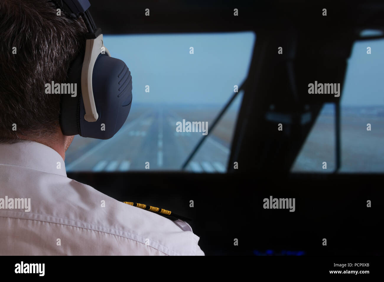 Close up of captain's epaulettes and headphones in the cockipt of commercial airplane - Stock Image