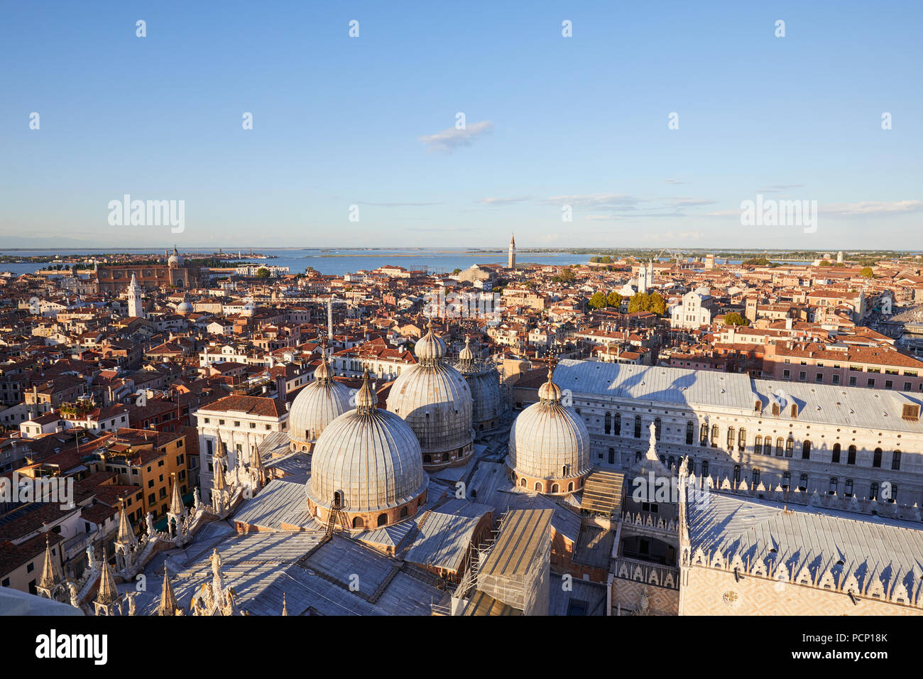 Aerial view of Venice rooftops, Saint Mark Basilica domes and horizon before sunset, Italy - Stock Image