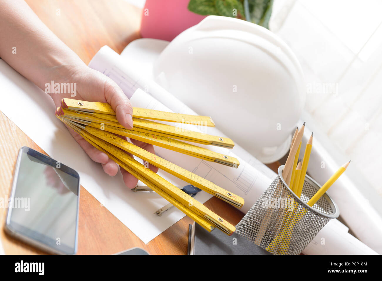 Construction plans in hand with measure, mobile phone, and drawing tools, helmet. - Stock Image