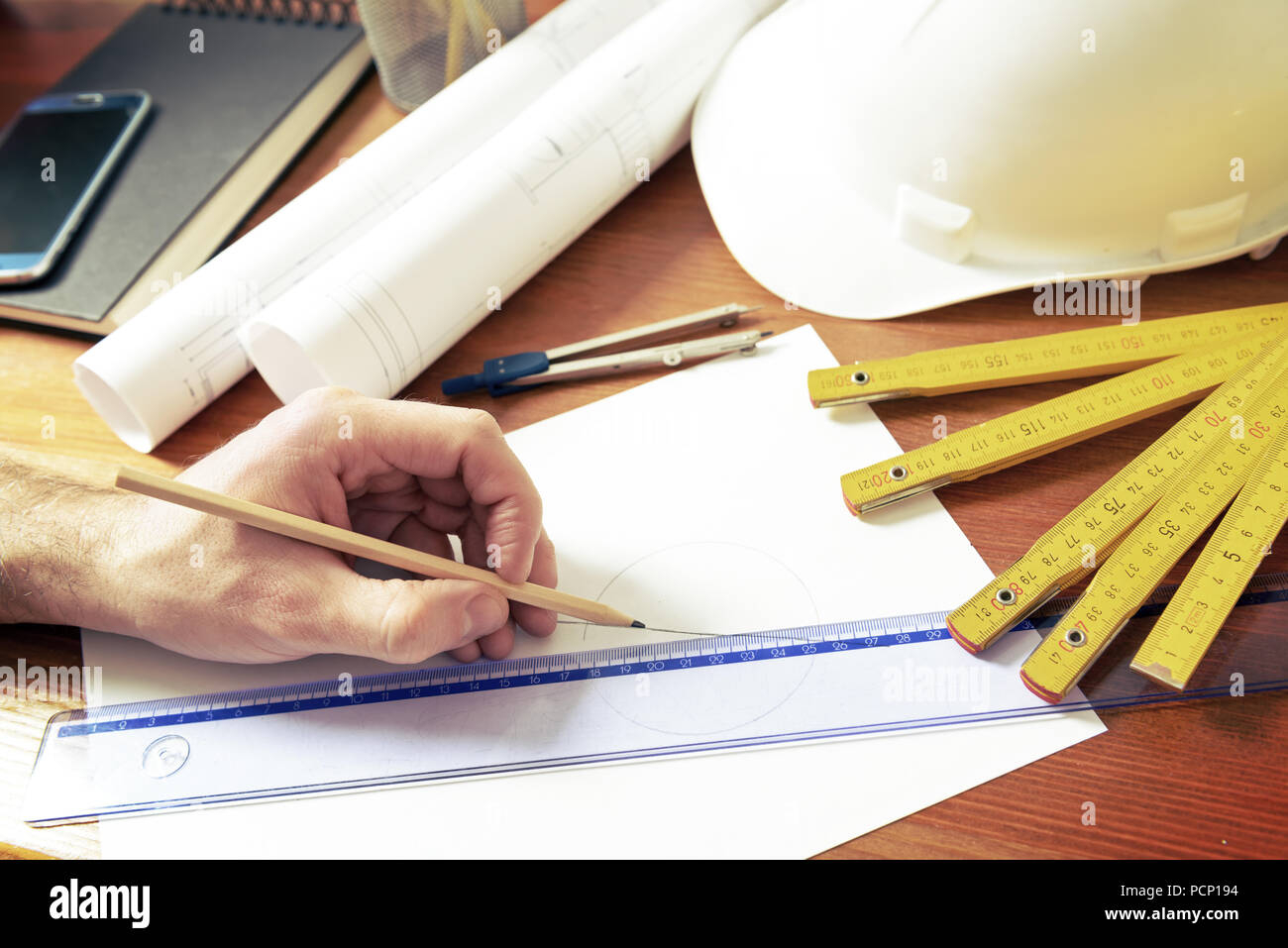 Hand drawing with pencil using ruler, construction plans with helmet, measure, mobile phone, and drawing tools - Stock Image