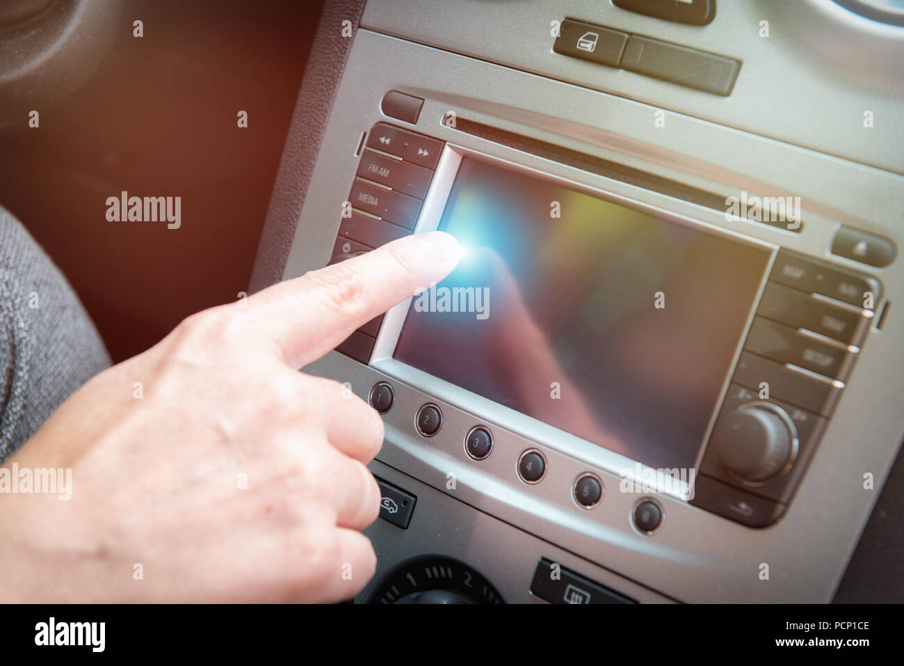 Driver using touchscreen to adjust car navigation or other systems settings - Stock Image