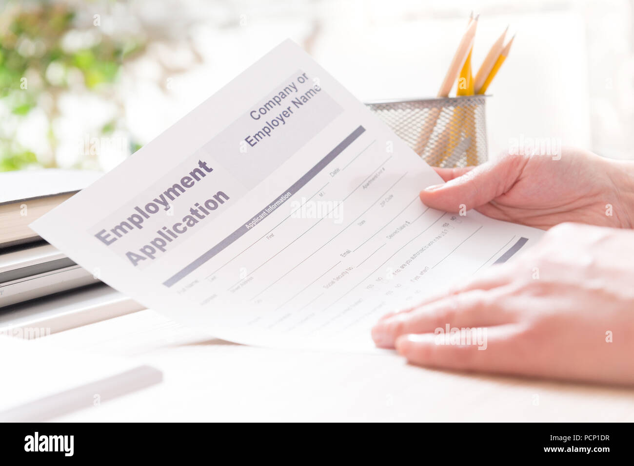blank employment application form in hands on a desk stock photo