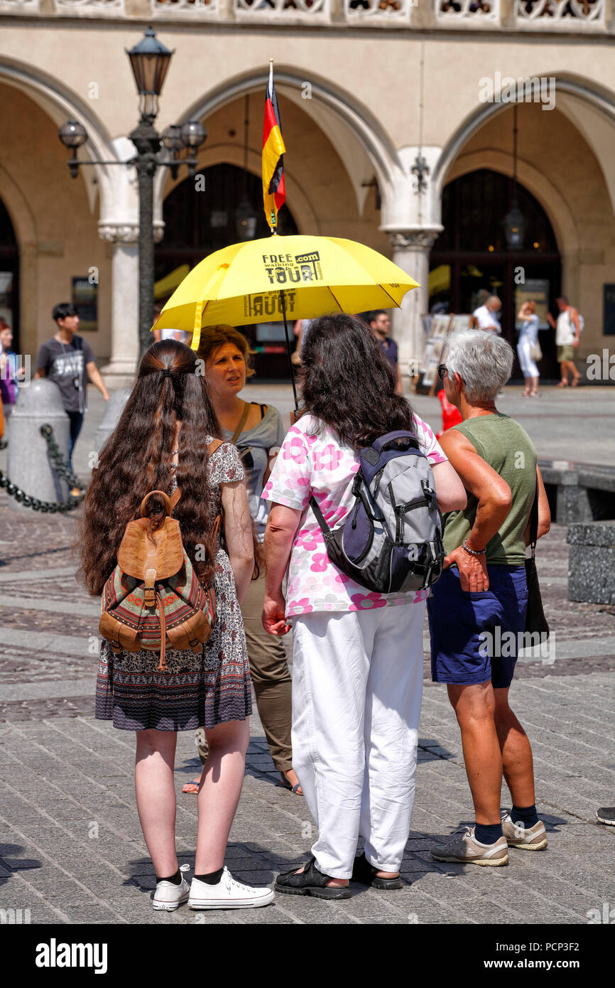 travel guide talking to people infront of Cloth Hall. old town krakow, lesser poland, poland, europe - Stock Image
