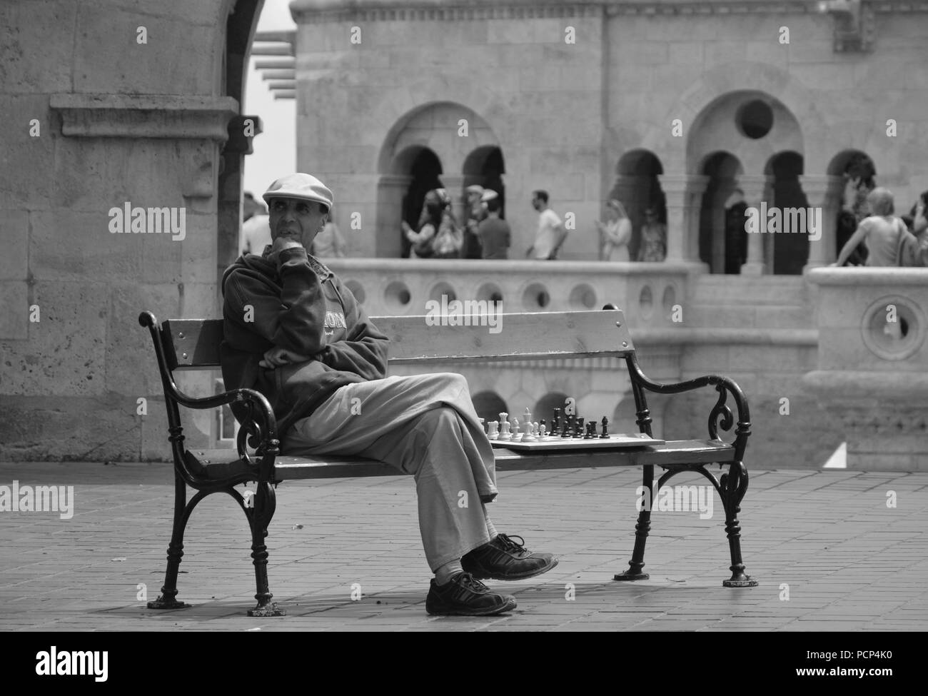 A chess player sitting on a bench and waiting some people to come and play with him at Fishermen's Bastion - Stock Image