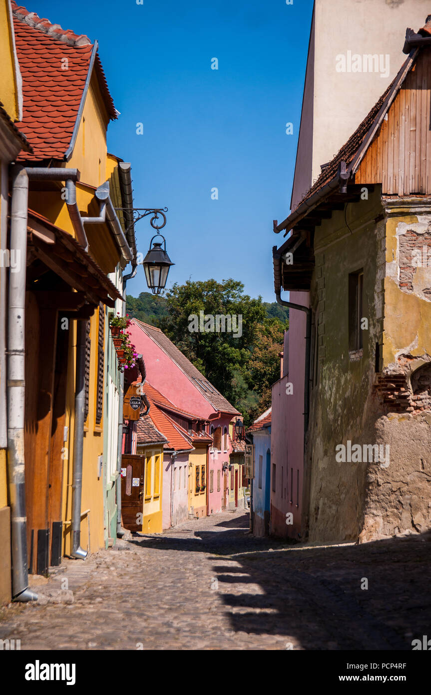 Narrow street in the old center of Sighisoara, Romania - Stock Image
