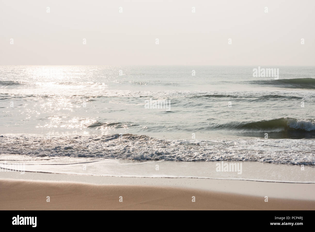 Glistening water on beach - Morning time on a tropical beach with glistening water and mild sea waves. - Stock Image
