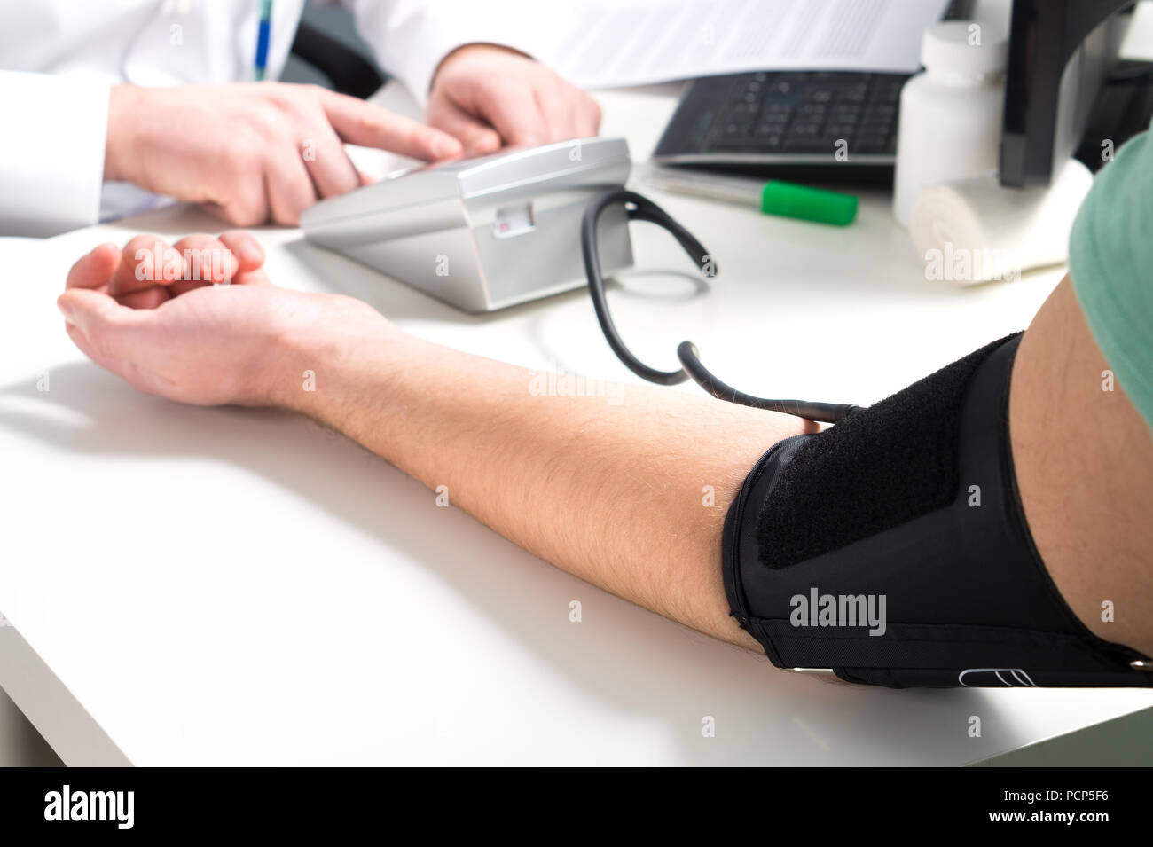 Doctor or nurse measure blood pressure of a patient with meter and monitor device. Hand and arm on emergency room or hospital office table. - Stock Image