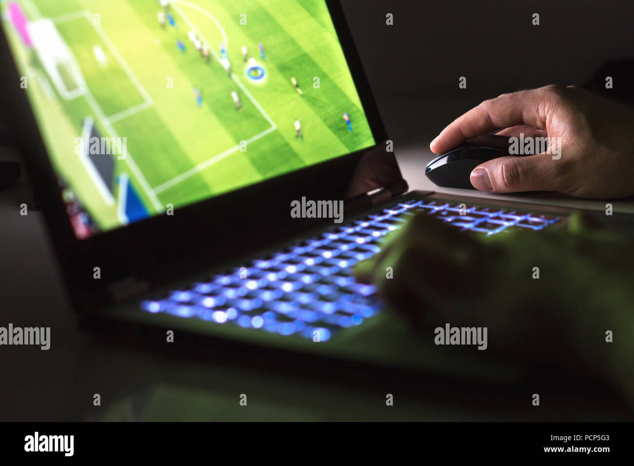 Young man playing soccer or football game online with laptop in dark or late at night. Competitive video gaming, electronic sports and esports concept - Stock Image