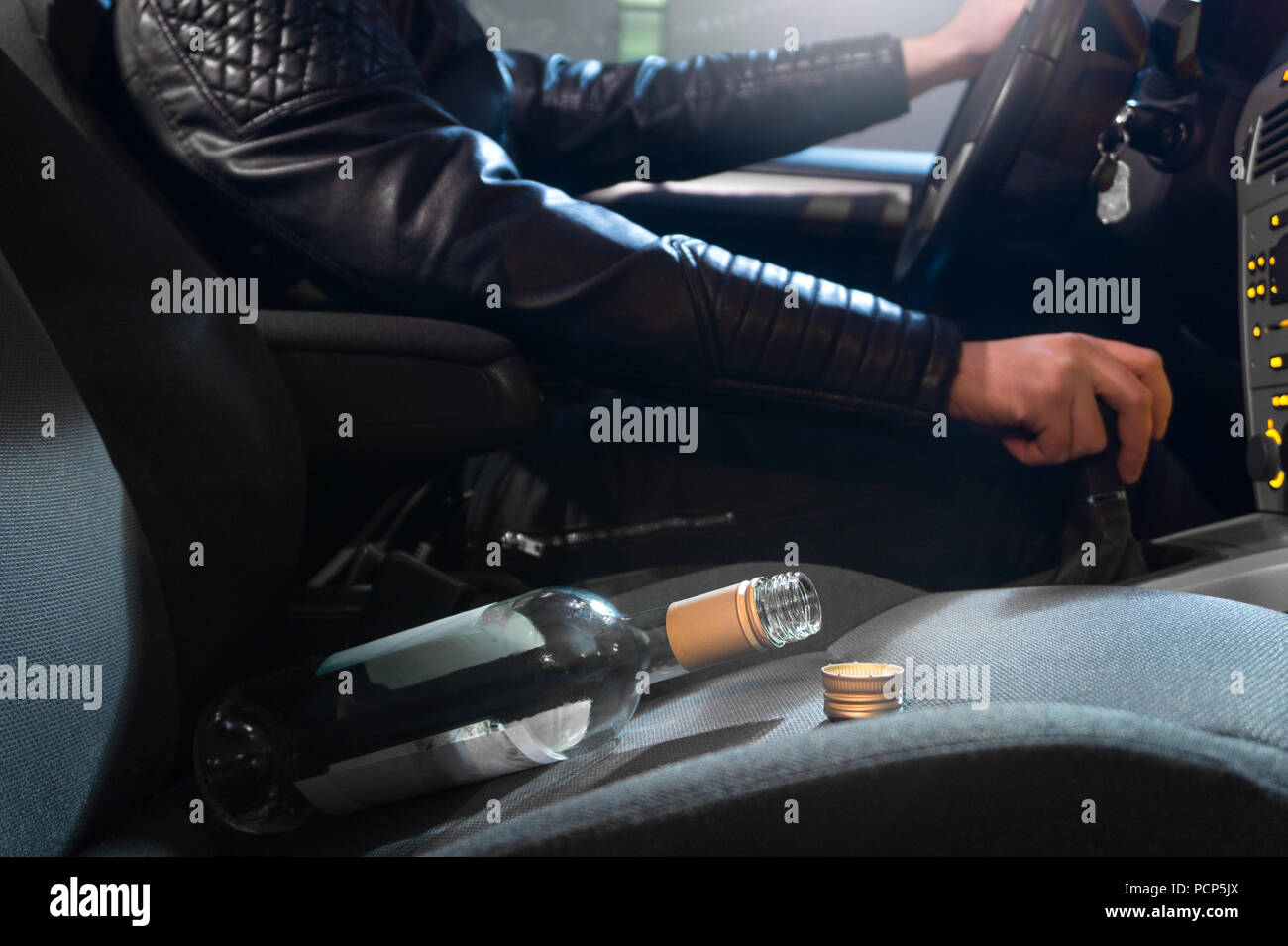 Drunk driving concept. Young man driving car under the influence of alcohol. Empty bottle of wine on front seat. Going away from party late at night.  - Stock Image