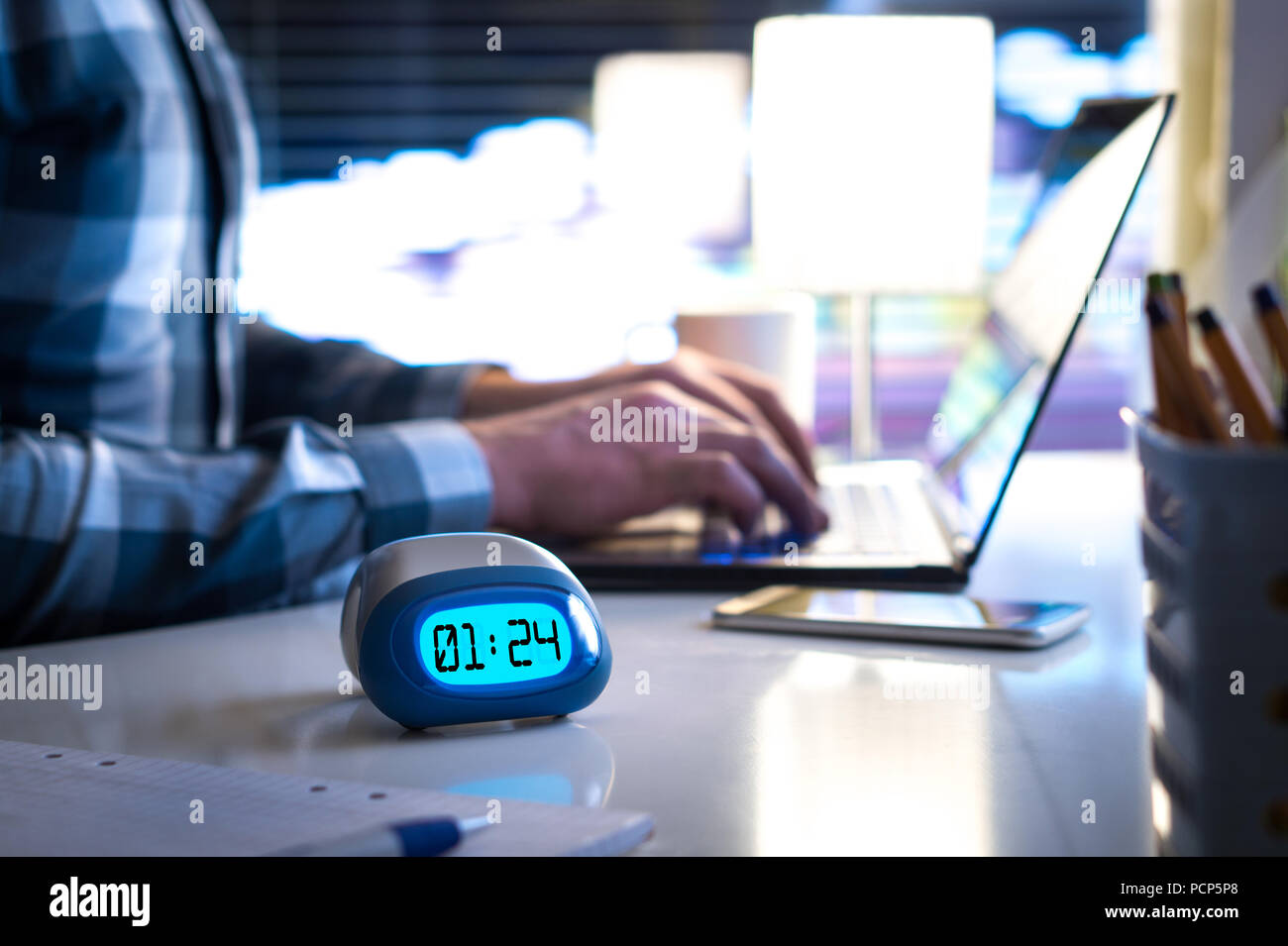 Man working late. Workaholic or being behind schedule concept. Business person in modern office building or home at night using laptop. - Stock Image